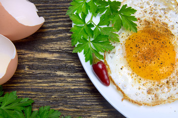 Fried egg with spices, green parsley on plate with pepper and eggshell close up, on vintage wooden background