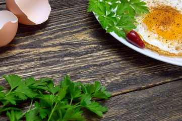 Fried egg with spices, green parsley on plate with pepper and eggshell, on vintage wooden background