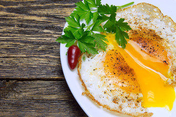 Sliced fried egg with spices, green parsley on plate with pepper on vintage wooden background