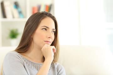 Pensive woman wondering at home