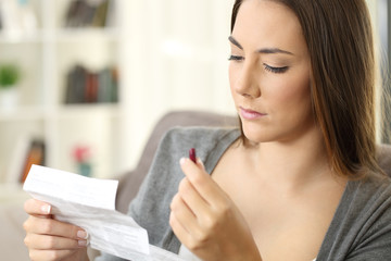 Serious woman holding a medicine reading a leaflet