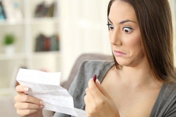 Shocked woman reading contraindications of a leaflet of a capsule