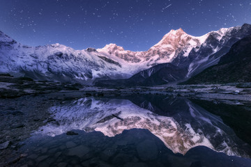 Poster Reflection Amazing night scene with himalayan mountains and mountain lake at starry night in Nepal. Landscape with high rocks with snowy peak and sky with stars reflected in water. Beautiful Manaslu, Himalayas