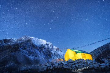 Wall Mural - Yellow glowing tent against high rocks with snowy peak and sky with stars at night in Nepal. The Himalayan Mountains. Landscape with mountains, starry sky and bivouac. Trekking in Himalayas. Travel