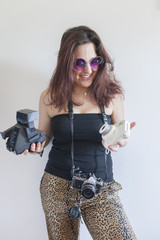 A young woman holding cameras