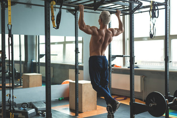 Muscular athlete man making Pull-up in gym. Bodybuilder training in fitness club showing his perfect back and shoulder muscles. Toned image