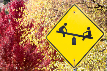 Caution playground sign against autumn leaves