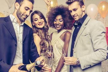 Mann öffnet eine Sektflasche bei Feier oder Party von Silvester oder Geburtstag in Club