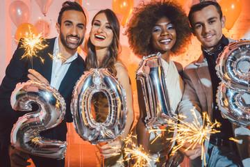 Männer und Frauen feiern das Neujahr 2018 mit Wunderkerzen und Sekt