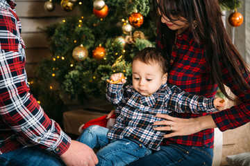 Christmas family portrait of young happy smiling parents playing with small child near the christmas tree. Winter holiday Xmas and New Year concept