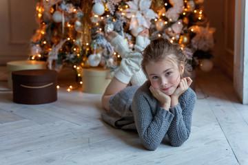 Young girl lies near a Christmas tree