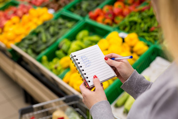Woman with notebook in grocery store, closeup. Shopping list on paper.
