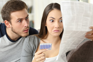 Suspicious couple reading a leaflet after taking contraceptive pills