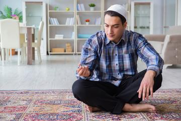 Young muslim man praying at home