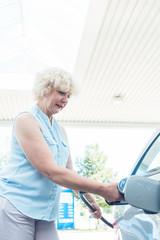 Senior Frau tankt Benzin oder Diesel in ihr Auto an der Tankstelle