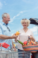 Fröhliches Rentnerpaar kauft im Supermarkt ein und lädt den Einkauf in den Kofferraum von Auto