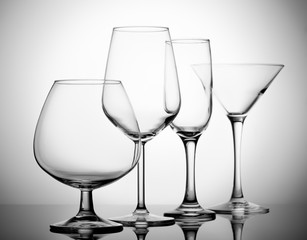 A variety of empty glasses for alcoholic beverages.