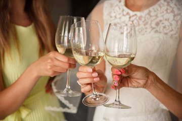 Wedding party, bride clinks to the bridesmaids with champagne glasses. Wedding or hen party concept