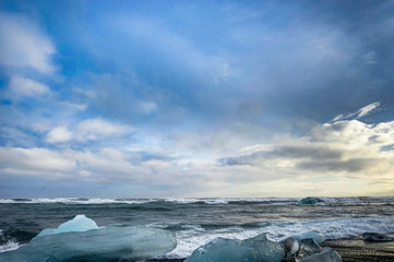 Icebergs floating in Jokulsarlon glacier lake at sunset in Icela