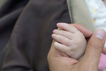 Newborn baby touching his father hand