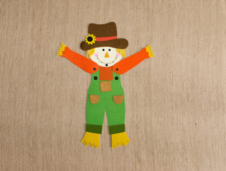 Felt Scarecrow decoration with Both Arms Up on Tan Background. He is wearing green overalls, an orange shirt and a brown hat adorned with a sunflower.
