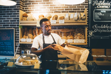 Black man sells in bakery.
