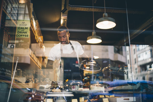 Black man works in pastry shop.