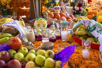 El altar de muertos tiene muchas frutas y objetos.