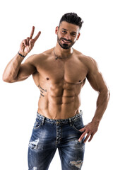 Handsome shirtless bodybuilder shot from above doing Victory sign with two fingers, standing isolated on white background