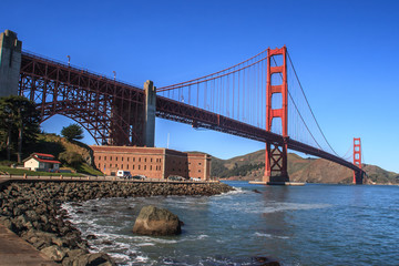 Golden Gate bridge from the San Francisco side. View of Fort Mason on the left and rocks in the foreground. A blue sky is in the background. It is a horizontal image.