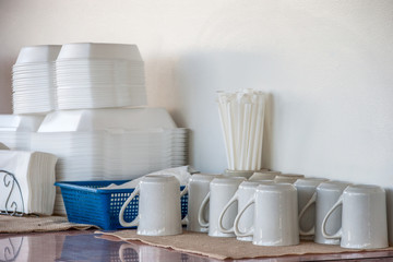 setup table in a restaurant with white mugs, straws standing up in container, a blue basket with napkins and starafoam containers. A white wall is in the background.