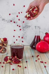 Pomegranate juice and fruit slices. Grains are flying over the glass. The concept of levitation