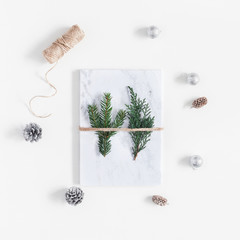Christmas composition. Marble gift and pine branches on white background. Christmas, winter, new year concept. Flat lay, top view, square