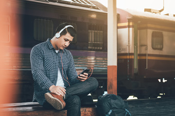 Hipster asian man listen music at train station.