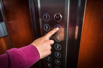 Woman pressing the button in the elevator interior