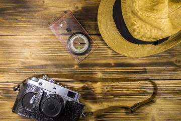 Compass, hat and retro photo camera on wooden background