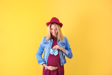 Beautiful pregnant woman with baby shoes on yellow background
