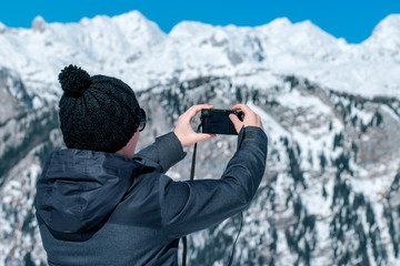 Female tourist taking picture of mountain landscape with compact camera