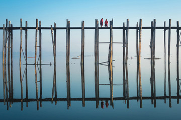 Buddhist monks crossing U Bein Bridge at sunrise in Amarapura, Mandalay, Myanmar (Burma).
