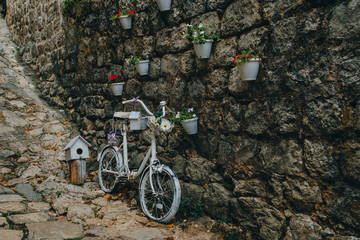 Bicycle decorated with flowers near the wall