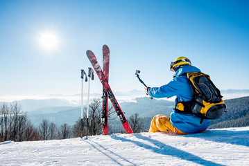 Rearview view of a skier with backpack and ski equipment sitting on the snow on top of the mountain taking selfies with his camera on a selfie stick while resting after skiing at the winter resort