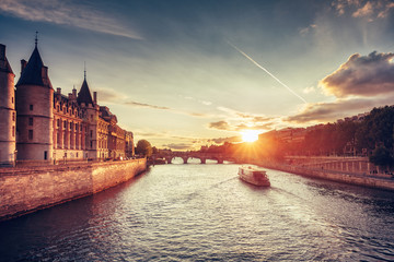 Beautiful skyline of Paris, France, with Conciergerie, Pont Neuf and cruise boat at sunset. Colourful travel background. Romantic cityscape.