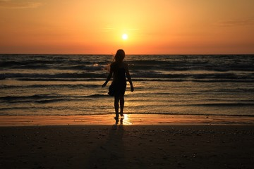 A little girl on the seaside sunset