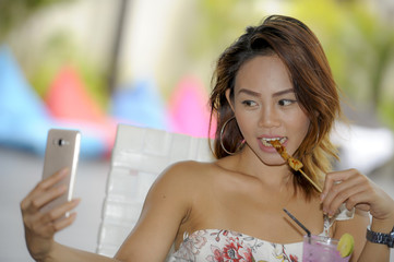 happy Asian girl in sexy dress having brunch or lunch at holiday resort outdoors taking selfie pic with mobile phone