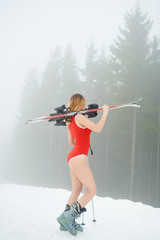 Attractive female skier wearing bodice, holding skis on the shoulder, standing on the snowy slope at ski resort in the mountains. Foggy forest on the background. Ski season and winter sports concept