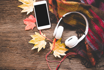 Cozy winter background, cup of hot coffee with marshmallow and headphone music, smart phone,warm knitted sweater, vintage tone.  Lifestyle and music concept.