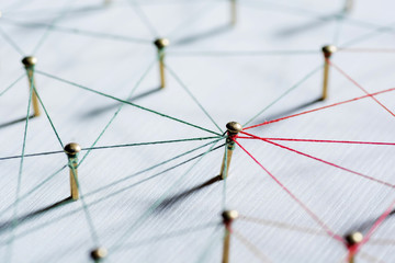 Background. Abstract concept idea of network, social media, internet, teamwork, communication. Thumbtacks linked together by red thread. Isolated. Entities connected.