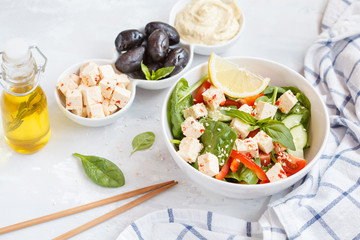 Vegan healthy salad with paprika tofu, hummus and olives