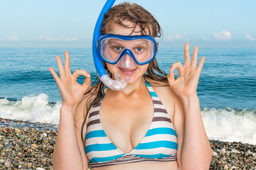 Woman with snorkeling mask for diving stands near the sea