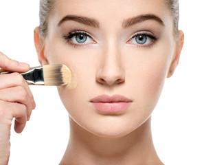 Girl applies  tonal foundation on face use makeup brush